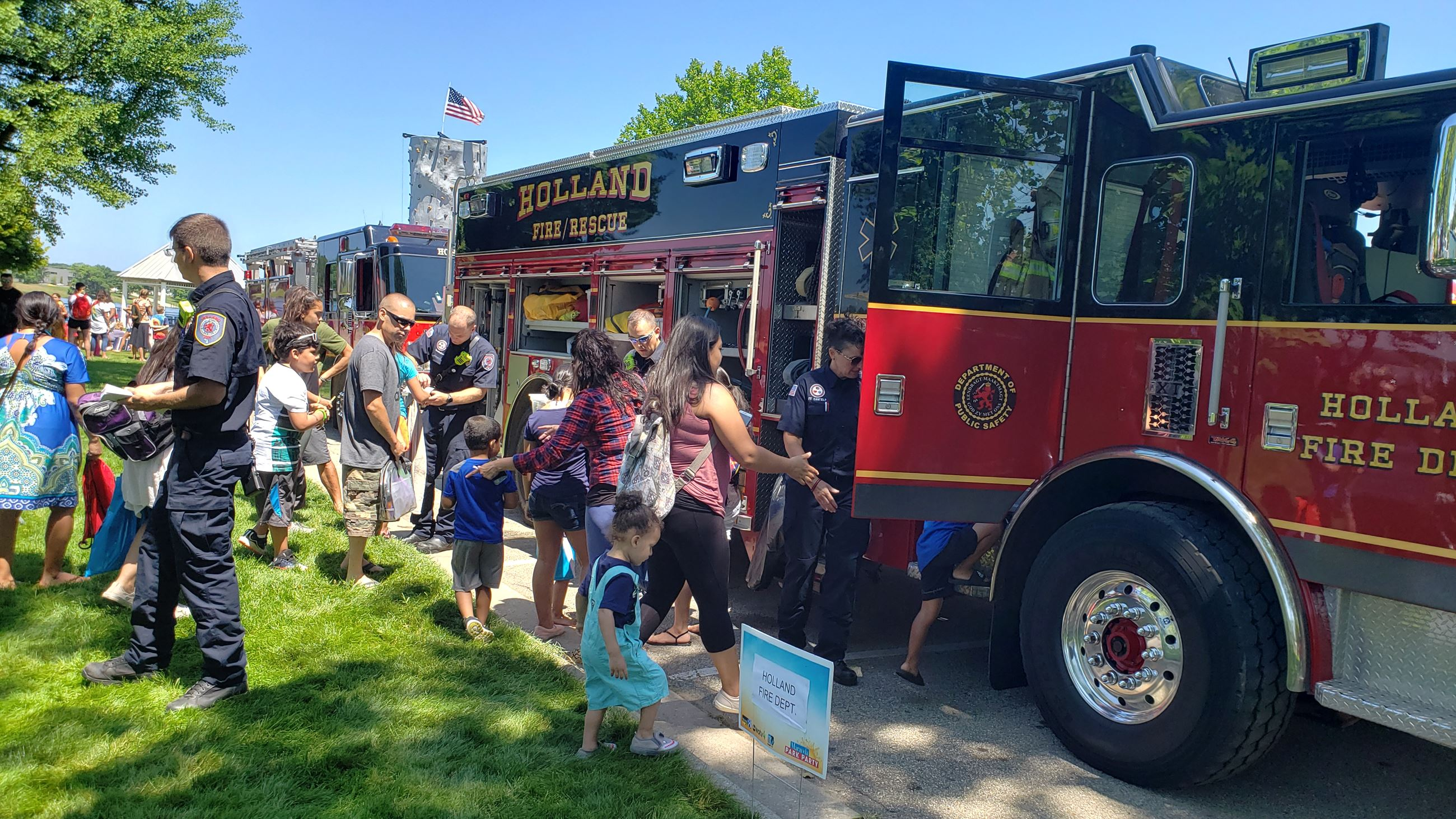 Fire trucks at a park with children and Firefighters around it