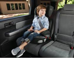 Child sitting in a car seat that is facing the front of the car, in the back seat of the car