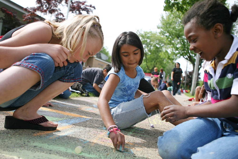 Young children making art with sidewalk chalk
